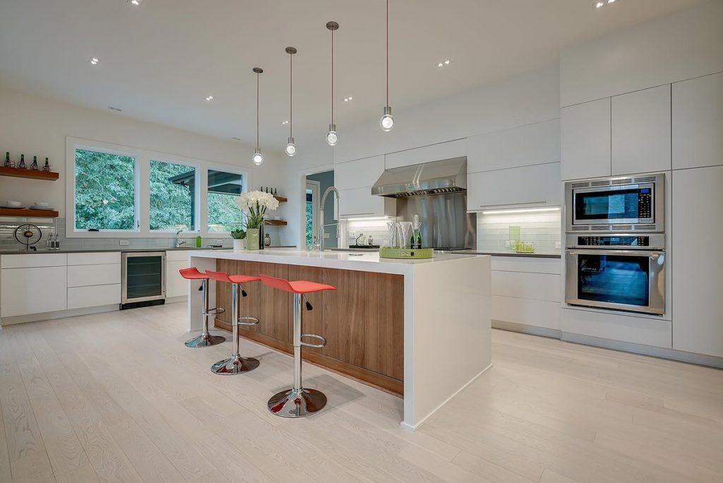 Ultra modern kitchen with water fall leg white quartz kitchen island and gray quartz countertops