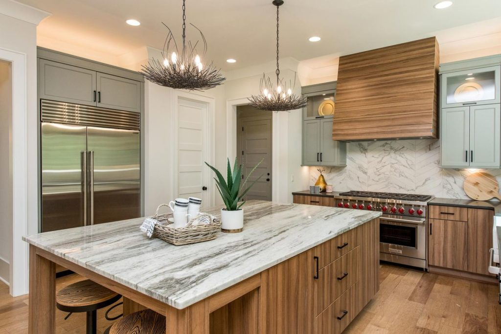 Modern kitchen with brushed wood hood, quartz kitchen island, and white porcelain tile backsplash