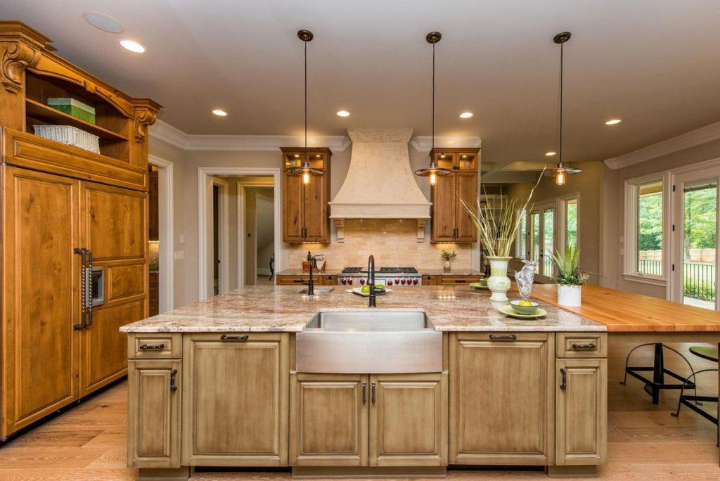 Warm kitchen with farmhouse sink, butchers block island and granite countertops
