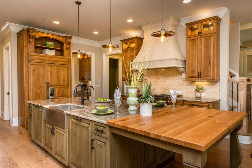 Warm kitchen with butchers block island and granite countertops