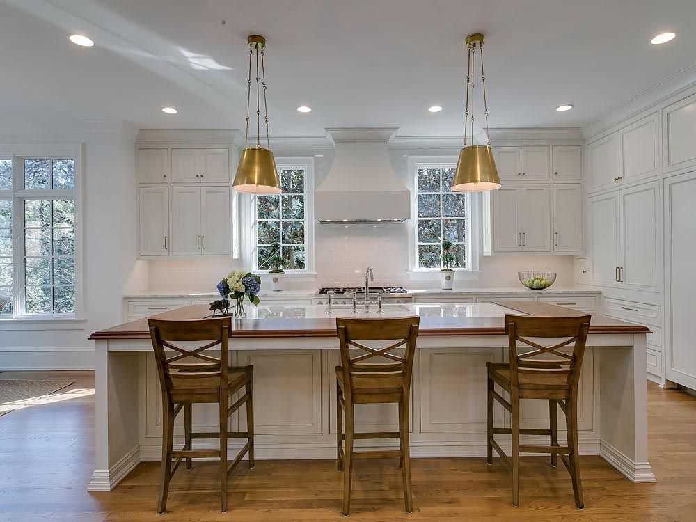 White kitchen with modern island featuring split wood and white granite countertop