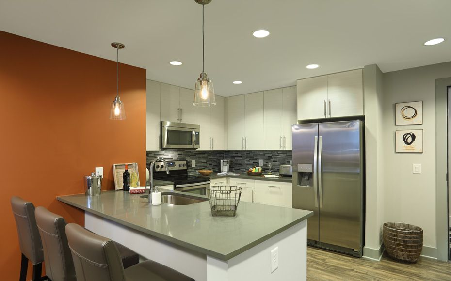 Modern apartment kitchen with white kitchen island featuring gray soapstone countertop and integrated sink