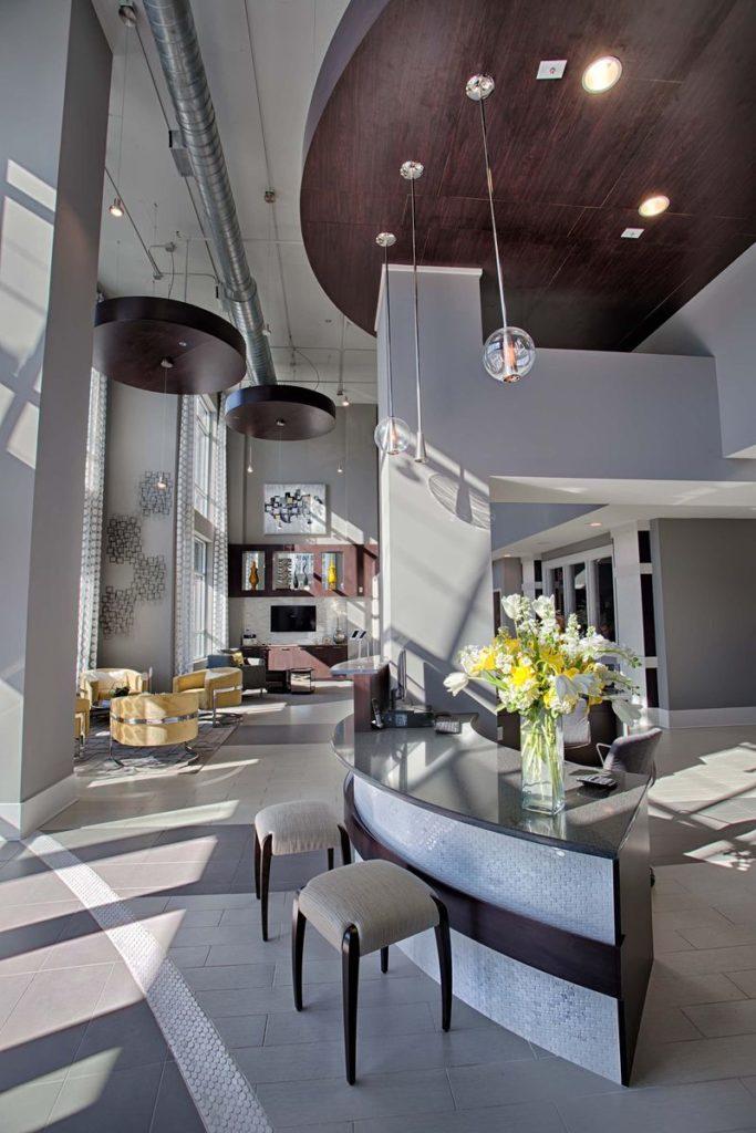 Curved apartment complex reception desk with dark gray quartz countertop