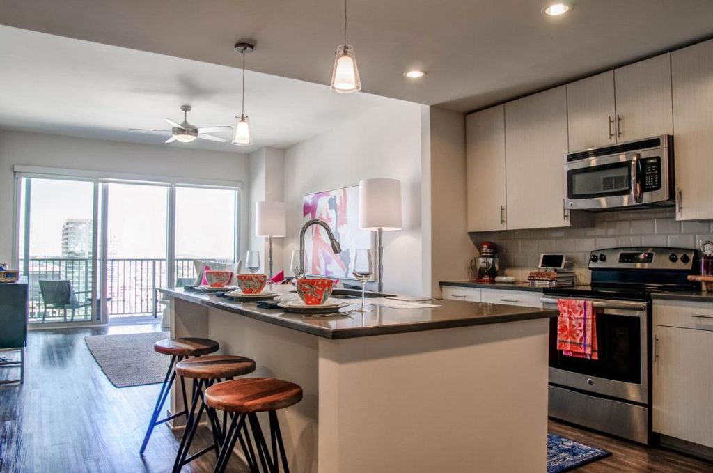 Modern apartment kitchen with white cabinets and kitchen island featuring gray soapstone countertops
