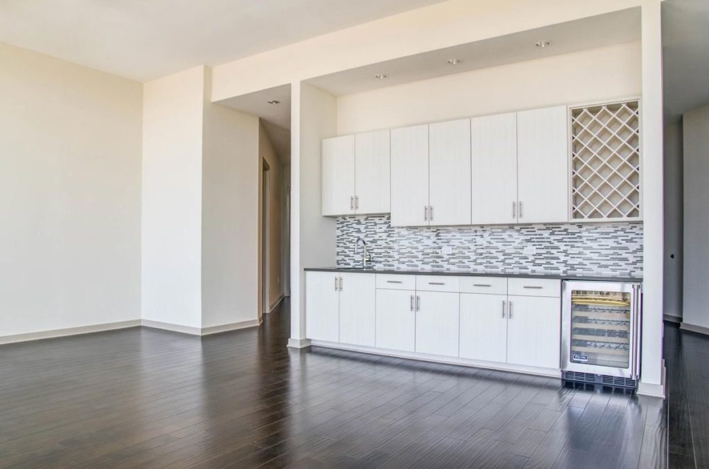 Apartment kitchen with built in wine fridge, white cabinets and gray soapstone countertops