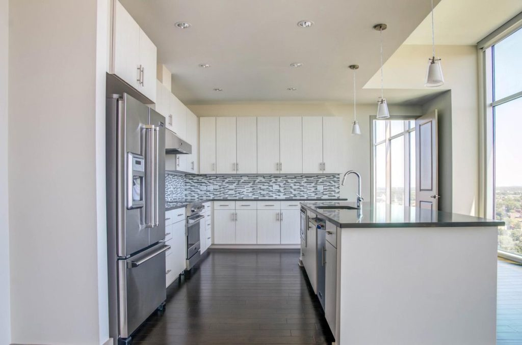 Sunny apartment kitchen with white cabinets and light gray soapstone countertops