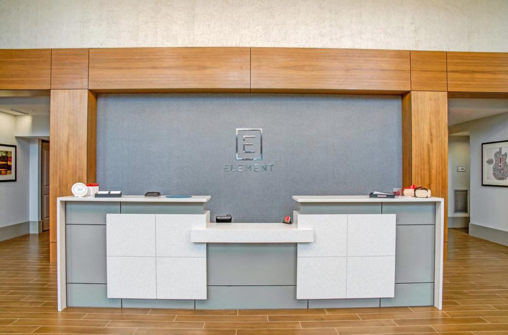 Apartment complex reception desk with white quartz countertop, waterfall legs, and light gray cabinets