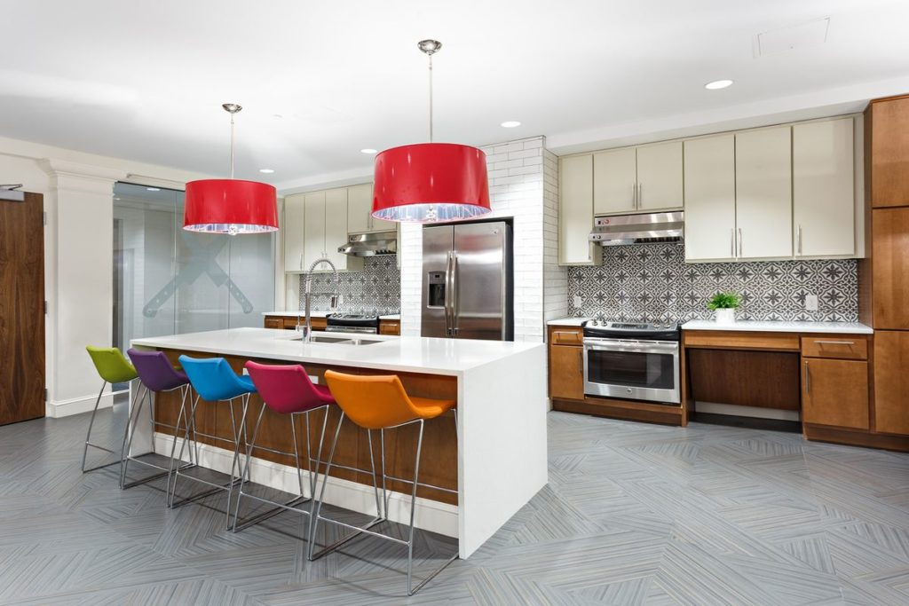 Trendy apartment kitchen with large white quartz kitchen island with waterfall legs and patterned tile backsplash