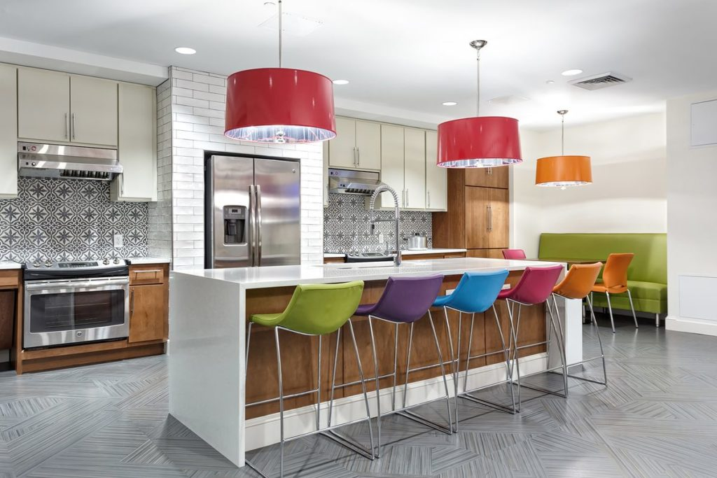 Funky apartment kitchen with large white quartz kitchen island with waterfall legs