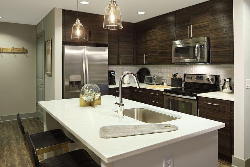 Medium sized apartment kitchen with mahogany cabinets and white soapstone kitchen island countertop