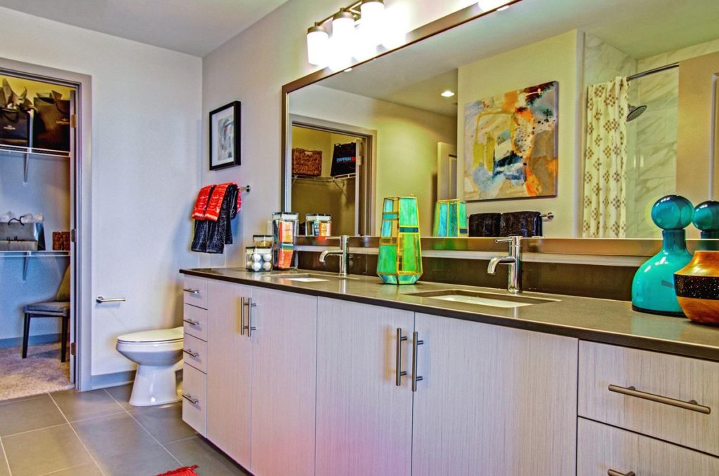 Master bathroom with light brushed wood grain cabinets and dark gray soapstone double vanity