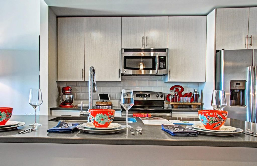 Apartment kitchen with dark gray soapstone topped kitchen island and white modern cabinets