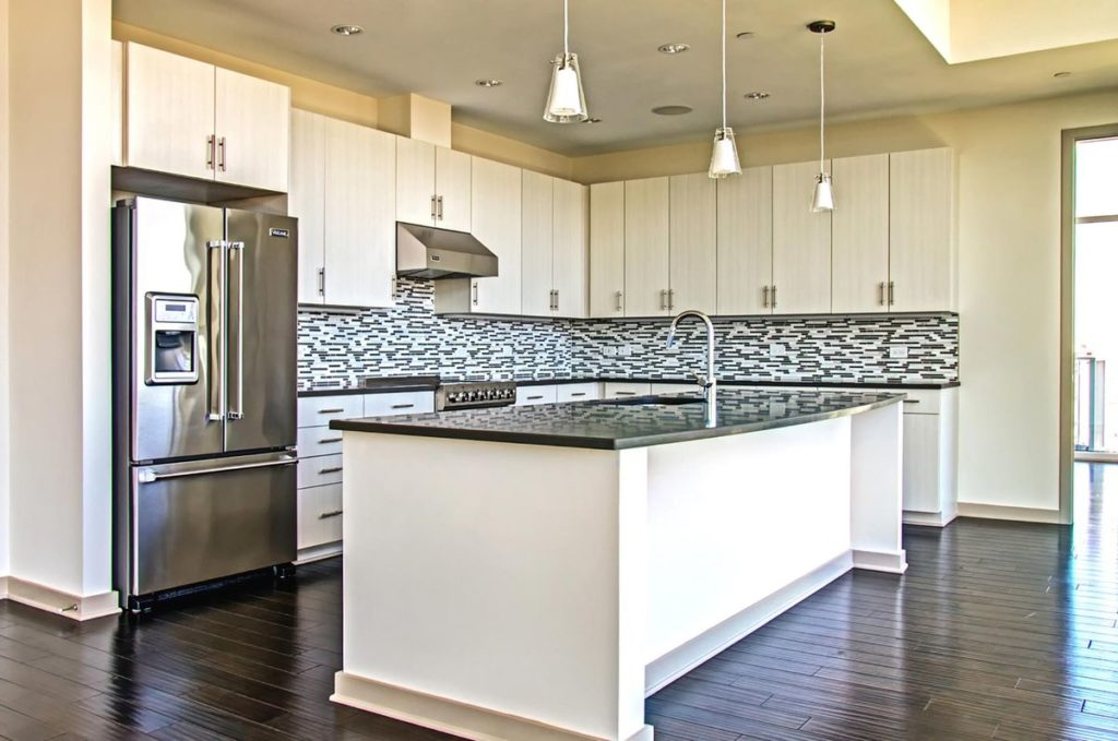Modern apartment kitchen with white cabinets and dark gray soapstone kitchen island