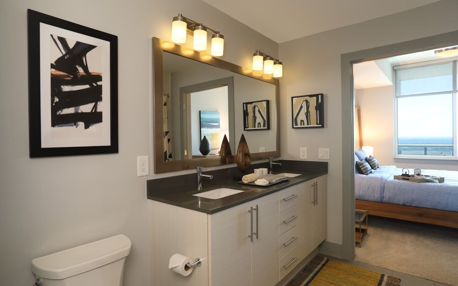 Apartment master bathroom with double sink vanity and dark gray soapstone countertops