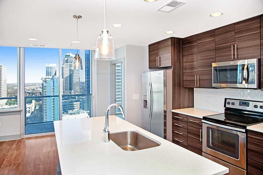 High rise apartment kitchen with built in sink kitchen island and white quartz countertop