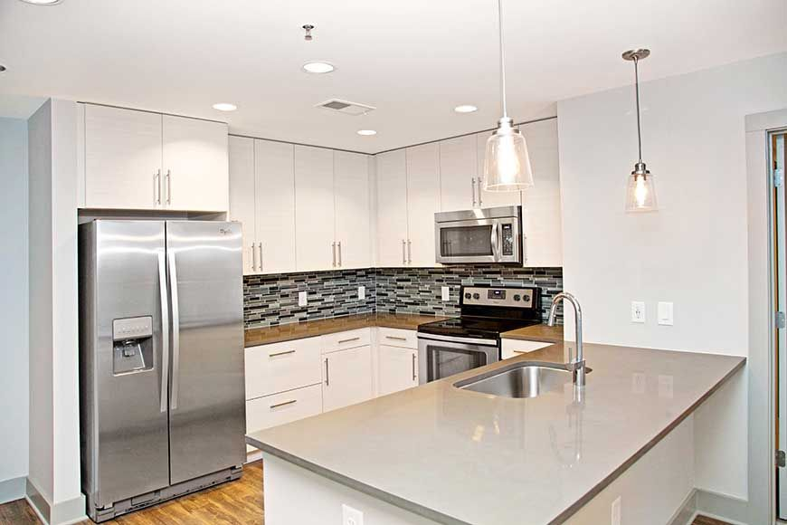 Apartment kitchen with light gray soapstone countertops and island
