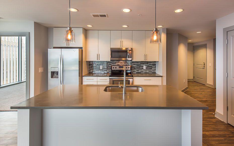 Apartment kitchen with kitchen island featuring dark gray soapstone countertop