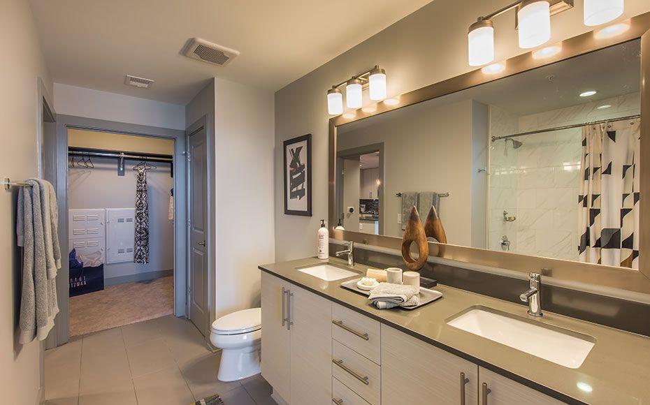 Apartment bathroom with porcelain tile shower backsplash and charcoal soapstone countertop vanity