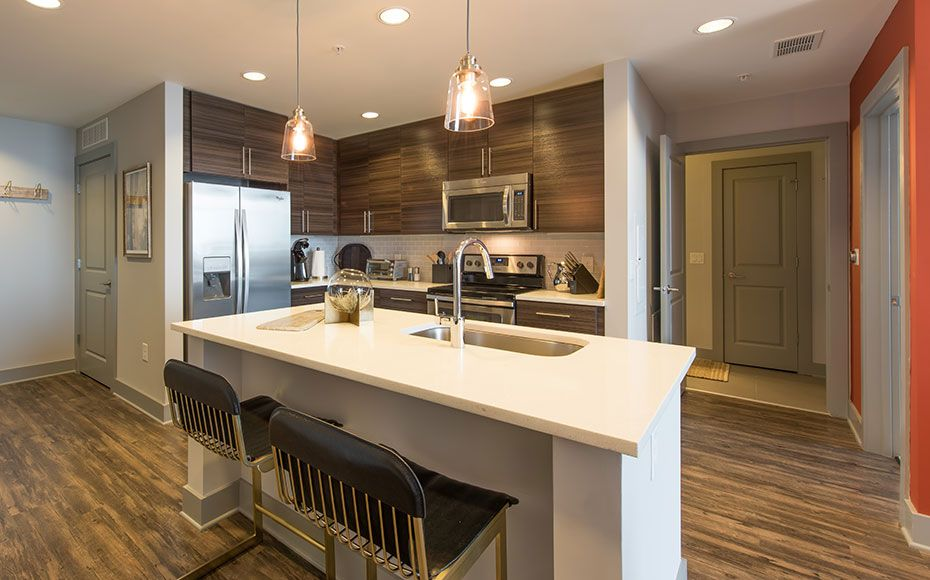 Kitchen with mahogany cabinets and white quartz kitchen island with built in sink