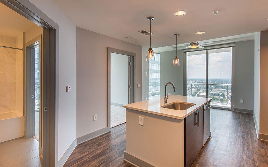 High rise apartment kitchen with white quartz kitchen island and porcelain tile shower backsplash