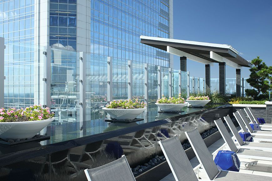Large apartment complex rooftop pool area with charcoal quartz water feature
