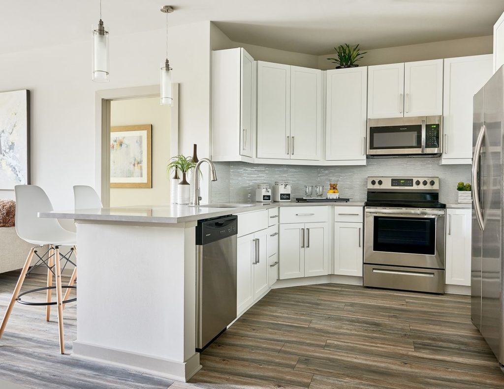 Apartment kitchen with white shaker cabinets and light gray soapstone countertops